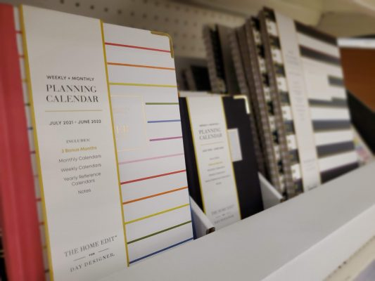Various sized planners with stripes on the covers.